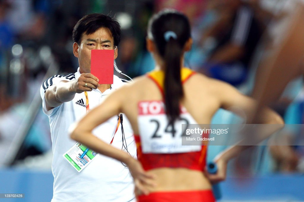 Yongli Wei of China is shown a red card and disqualified by the chief judge after false starting during the women's 4x100 metres heats during day...