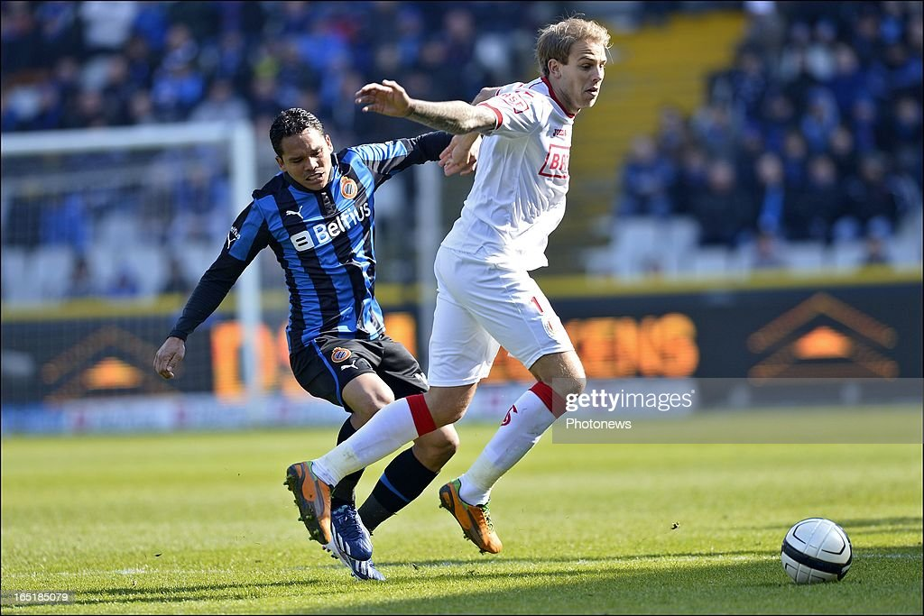 Yoni Buyens of Standard is challenged by Carlos Bacca of Club Brugge KV during the Jupiler League match between Club Brugge and Standard de Liege on April 01, 2013 in the Jan Breydel Stadium in Brugge, Belgium.