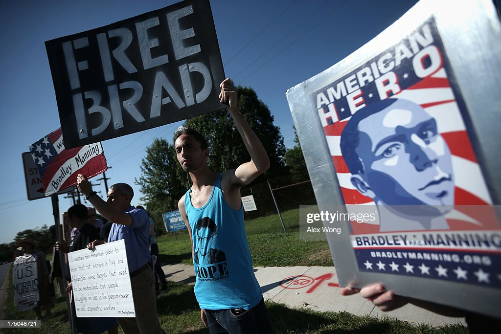 Yoni Miller (R) of Social Movement Technologies, along with other supporters of U.S. Army Pfc. Bradley E. Manning, hold signs to show support during a demonstration outside the main gate of Ft. Meade July 30, 2013 in Maryland. Military Judge Col. Denise Lind, who is presiding in the case of United States vs. Pfc. Bradley E. Manning, has reached a verdict and she is scheduled to read the verdict at 1pm today. Manning could face a life sentence for charges of espionage, aiding the enemy and computer fraud, for passing classified documents to WikiLeaks.