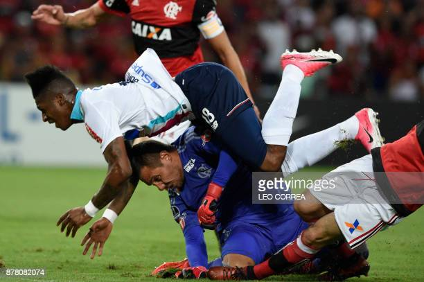 Yony Gonzalez of Colombia's Junior de Barranquilla falls on top of goalkeeper Diego Alves of Brazil's Flamengo during their Copa Sudamericana 1st leg...