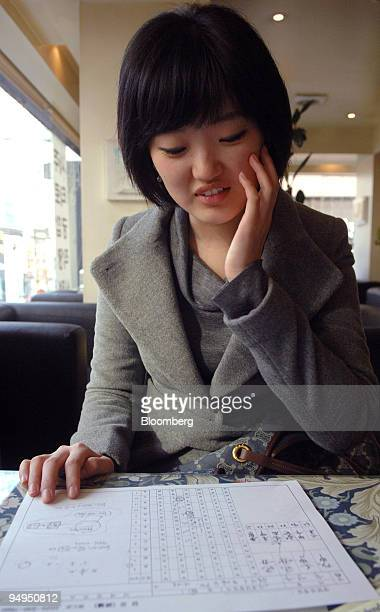 Yoo Young Joo a senior at college consults a piece of paper outlining her fortune following her meeting with a fortune teller at Saju Cafe a fortune...
