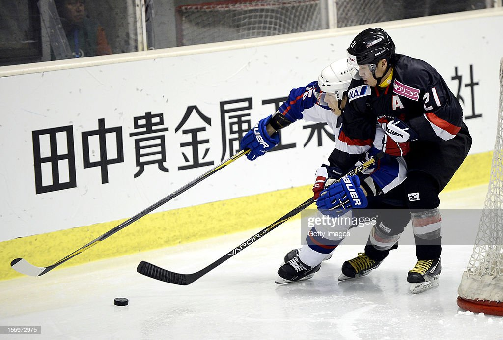 Yoon Kyungwon #15 of South Korea is defended by Shuhei Kuji #21 of Japan during the Ice Hockey Sochi Olympic Pre-Qualification Group J match between Japan and South Korea at Nikko Kirifuri Ice Arena on November 10, 2012 in Nikko, Tochigi, Japan. Japan won after over time 3-2.