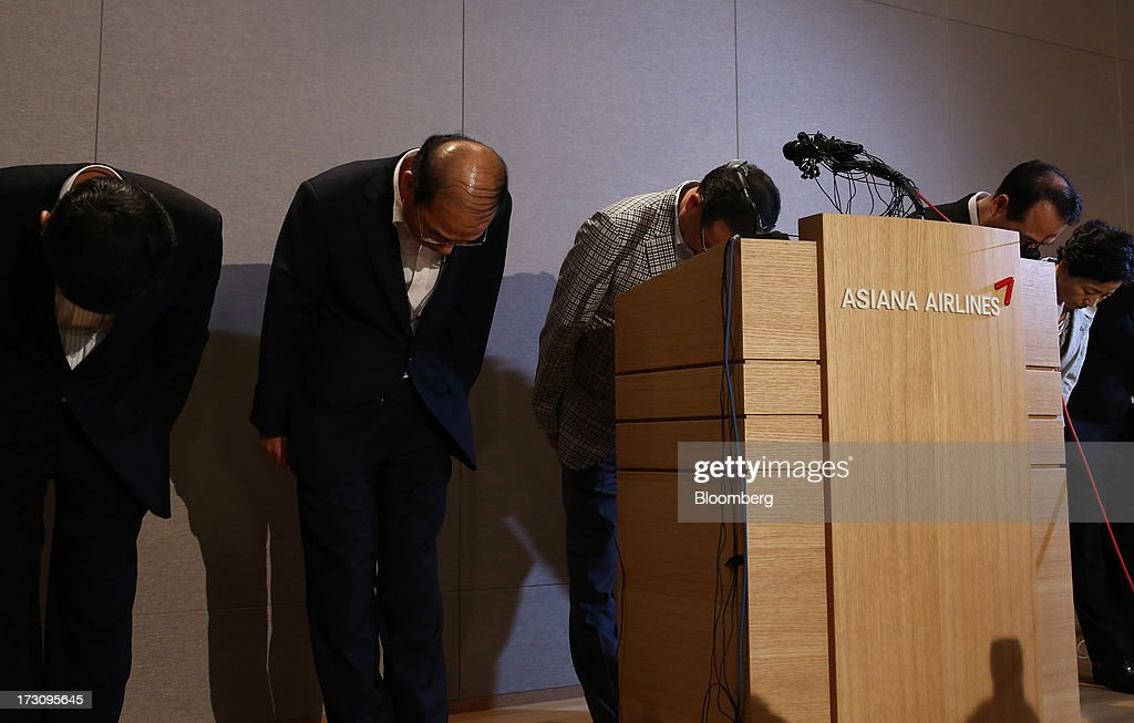 Yoon Young Doo, chief executive officer and president of Asiana Airlines Inc., third left, and company executives bow during a news conference at the company's headquarters in Seoul, South Korea, on Sunday, July 7, 2013. A Boeing Co. 777 flown by South Korea's Asiana Airlines crashed while landing in San Francisco yesterday, killing two people as passengers escaped down emergency slides before a fire swept through the plane. Yoon apologized for the crash and said that Asiana is struggling to confirm details of casualities through the U.S. authorities. Photographer: SeongJoon Cho/Bloomberg via Getty Images