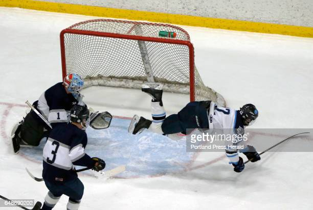 York junior Jacob Martin gets tripped up in the crease by CapeYarmouth goalie Dan Latham during the Class B South boys hockey semifinal