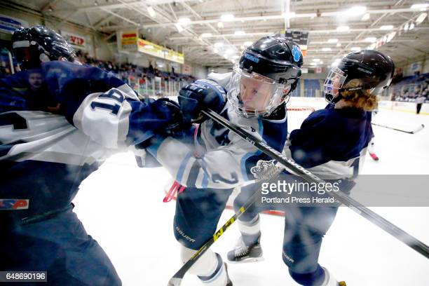 York junior Thomas Carr gets double checked by CapeYarmouth players Caleb Morrison left and Spencer King during the Class B South boys hockey...