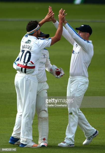 Yorkshire's Jack Brooks celebrates taking the wicket of Surrey's Rory Burns with team mates Andy Hodd and Shaun Marsh during day one of the...