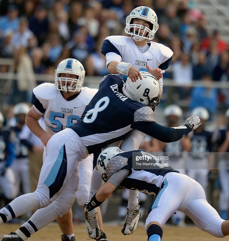 Yorktown's QB Will Roebuck, is hit by Stone Bridge defender Drew Dettra , left, and Luke Fitzgerald, right, after throwing as pass as Stone Bridge defeats Yorktown 69 - 50 in the Virginia AAA Northern Region Division 5 final at Stone Bridge High School in Ashburn VA, November 23, 2012 .