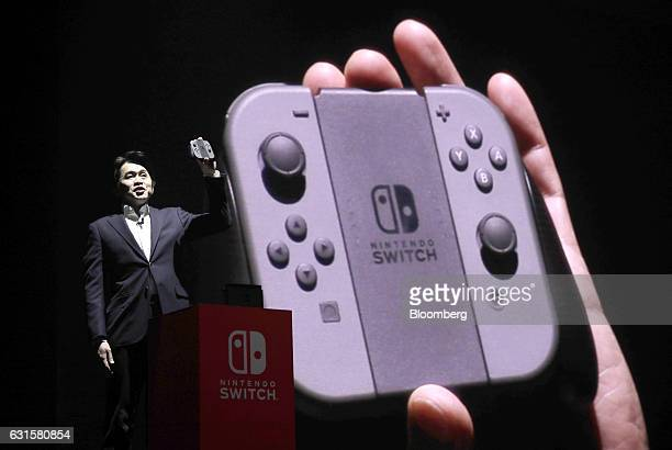 Yoshiaki Koizumi software development producer at Nintendo Co presents the company's Switch game console during an unveiling event in Tokyo Japan on...