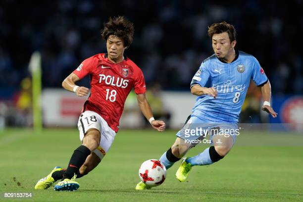 Yoshiaki Komai of Urawa Red Diamonds and Hiroyuki Abe of Kawasaki Frontale compete for the ball during the JLeague J1 match between Kawasaki Frontale...