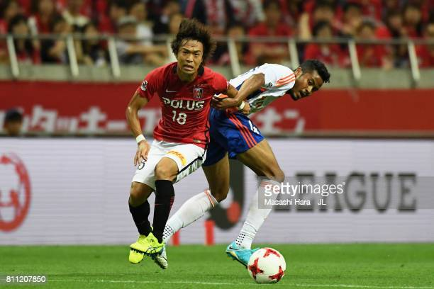 Yoshiaki Komai of Urawa Red Diamonds and Musashi Suzuki of Albirex Niigata compete for the ball during the JLeague J1 match between Urawa Red...