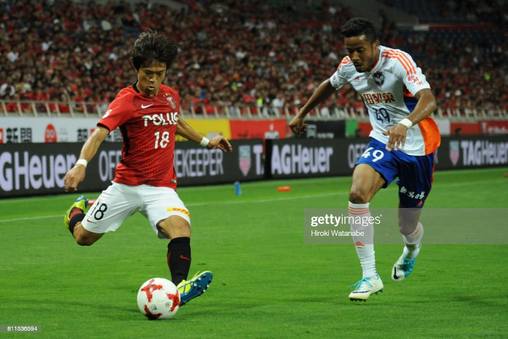 Yoshiaki Komai #18 of Urawa Red Diamonds and Musashi Suzuki #49 of Albirex Niigata compete for the ball during the J.League J1 match between Urawa Red Diamonds and Albirex Niigata at Saitama Stadium on July 9, 2017 in Saitama, Japan.