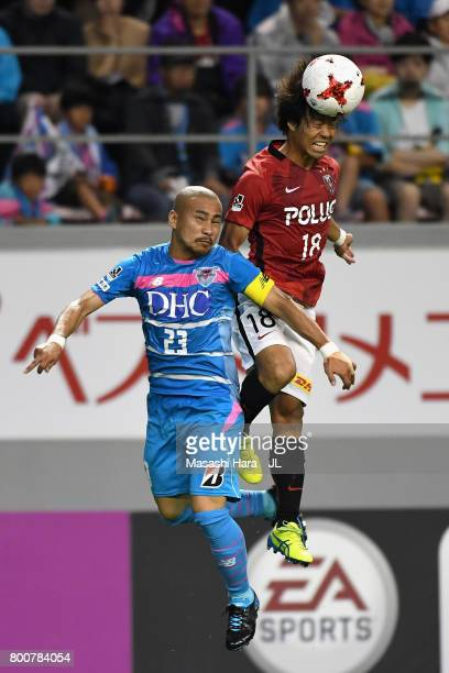 Yoshiaki Komai of Urawa Red Diamonds and Yutaka Yoshida of Sagan Tosu compete for the ball during the JLeague J1 match between Sagan Tosu and Urawa...