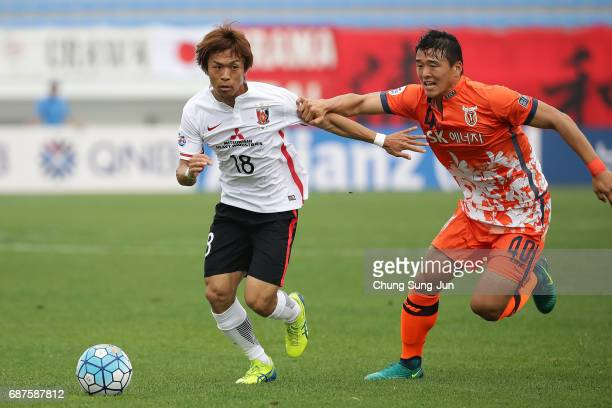 Yoshiaki Komai of Urawa Red Diamonds competes for the ball with Lee ChanDong of Jeju United FC during the AFC Champions League Round of 16 match...