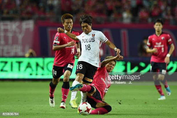 Yoshiaki Komai of Urawa Red Diamonds is tackled by Yoichiro Kakitani of Cerezo Osaka during the JLeague J1 match between Cerezo Osaka and Urawa Red...