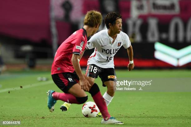 Yoshiaki Komai of Urawa Red Diamonds takes on Yoichiro Kakitani of Cerezo Osaka during the JLeague J1 match between Cerezo Osaka and Urawa Red...