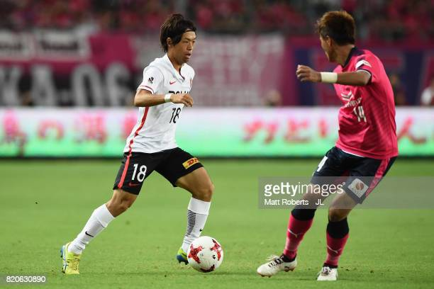 Yoshiaki Komai of Urawa Red Diamonds takes on Yusuke Maruhashi of Cerezo Osaka during the JLeague J1 match between Cerezo Osaka and Urawa Red...