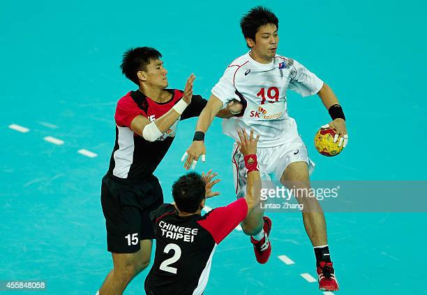 Yoshiaki Nomura of Japan is defended by HsienMing Hsu and ChiaWei Weng of Chinese Taibei during the Handball Men's Group D match between Chinese...