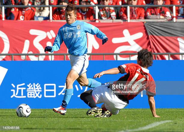 Yoshiaki Ota of Jubilo Iwata is tackled by Takahito Soma of Urawa Red Diamonds during the 86th Emperor's Cup quarter final match between Urawa Red...