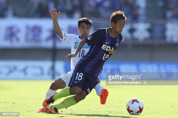 Yoshifumi Kashiwa of Sanfrecce Hiroshima and Chanathip Songkrasin of Consadole Sappporo compete for the ball during the JLeague J1 match between...