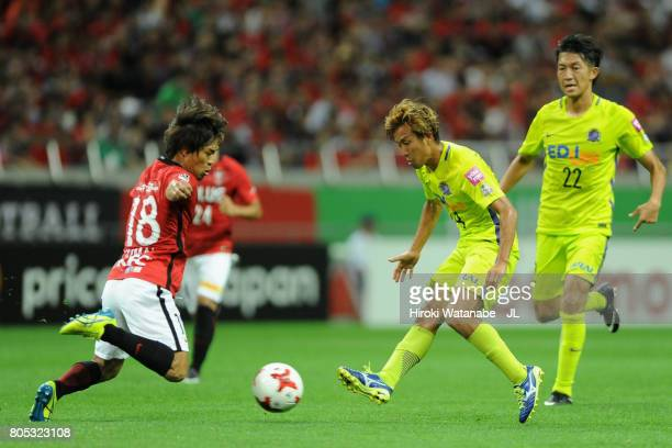 Yoshifumi Kashiwa of Sanfrecce Hiroshima and Yoshiaki Komai compete for the ball during the JLeague J1 match between Urawa Red Diamonds and Sanfrecce...