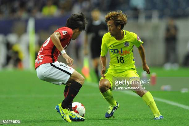 Yoshifumi Kashiwa of Sanfrecce Hiroshima takes on Yoshiaki Komai of Urawa Red Diamonds during the JLeague J1 match between Urawa Red Diamonds and...