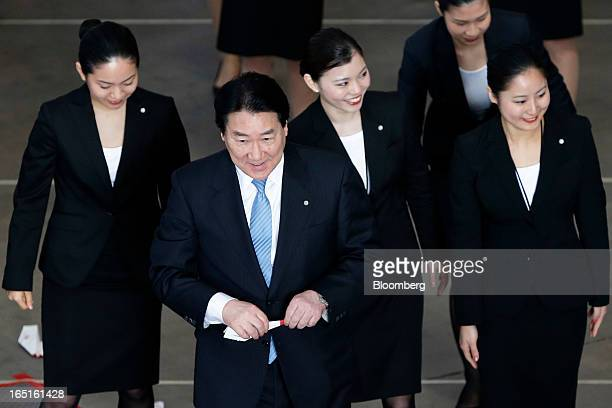 Yoshiharu Ueki president of Japan Airlines Co second from left walks with JAL group companies' new employees during a welcoming ceremony at the...
