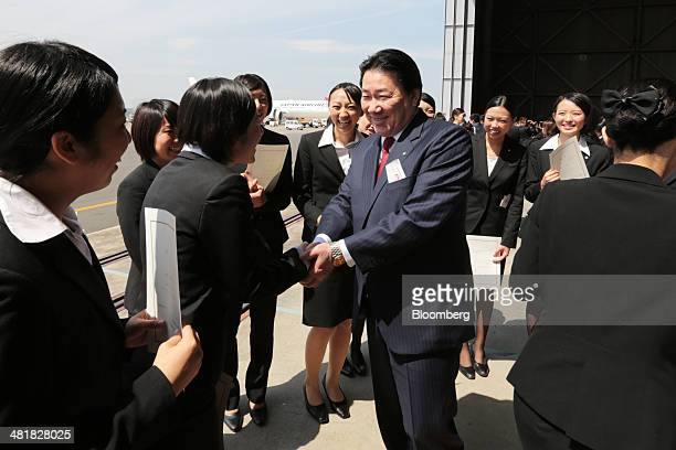Yoshiharu Ueki president of Japan Airlines Co shakes hands with JAL group companies' new employees following a welcoming ceremony at the company's...