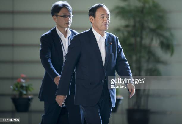 Yoshihide Suga Japan's chief cabinet secretary right arrives for a cabinet meeting at the Prime Minister's Official Residence in Tokyo Japan on...