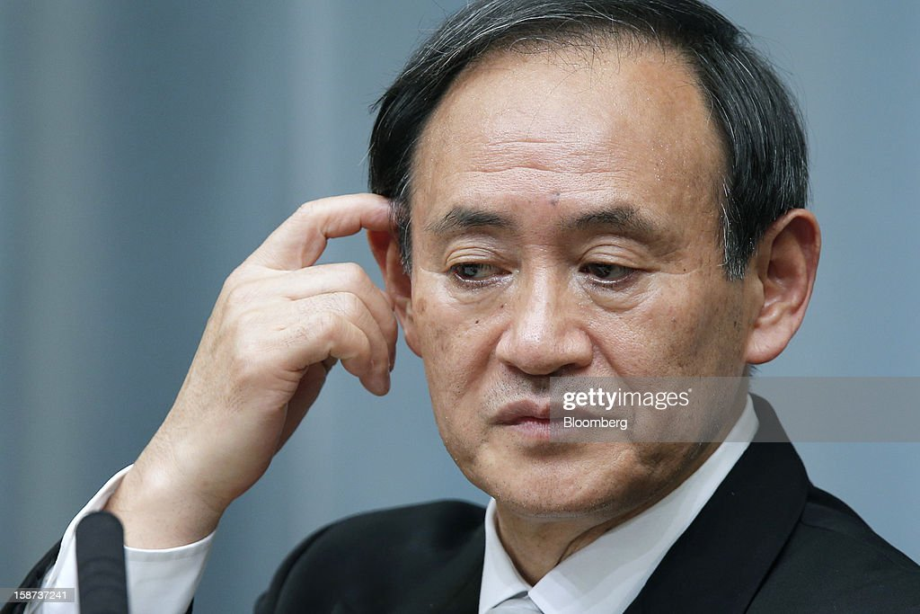 Yoshihide Suga, Japan's newly appointed chief cabinet secretary, pauses during a news conference at the prime minister's official residence in Tokyo, Japan, on Thursday, Dec. 27, 2012. Japan's parliament confirmed Shinzo Abe as the nation's seventh prime minister in six years, returning him to the office he left in 2007 after his party regained power in a landslide election victory last week. Photographer: Kiyoshi Ota/Bloomberg via Getty Images