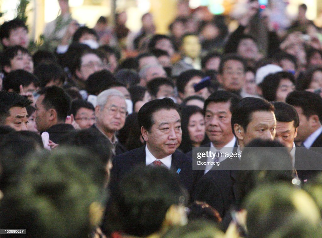 Yoshihiko Noda, Japan's prime minister and president of the Democratic Party of Japan (DPJ), center, arrives for a campaign rally for the Dec. 16 general election in Kawasaki City, Kanagawa Prefecture, Japan, on Saturday, Nov. 24, 2012. The government taking office after Japan's Dec. 16 election will pick the central bank's top three jobs, a chance to reshape policy in the third-largest economy that the opposition aims to seize for unlimited stimulus. Photographer: Tomohiro Ohsumi/Bloomberg via Getty Images