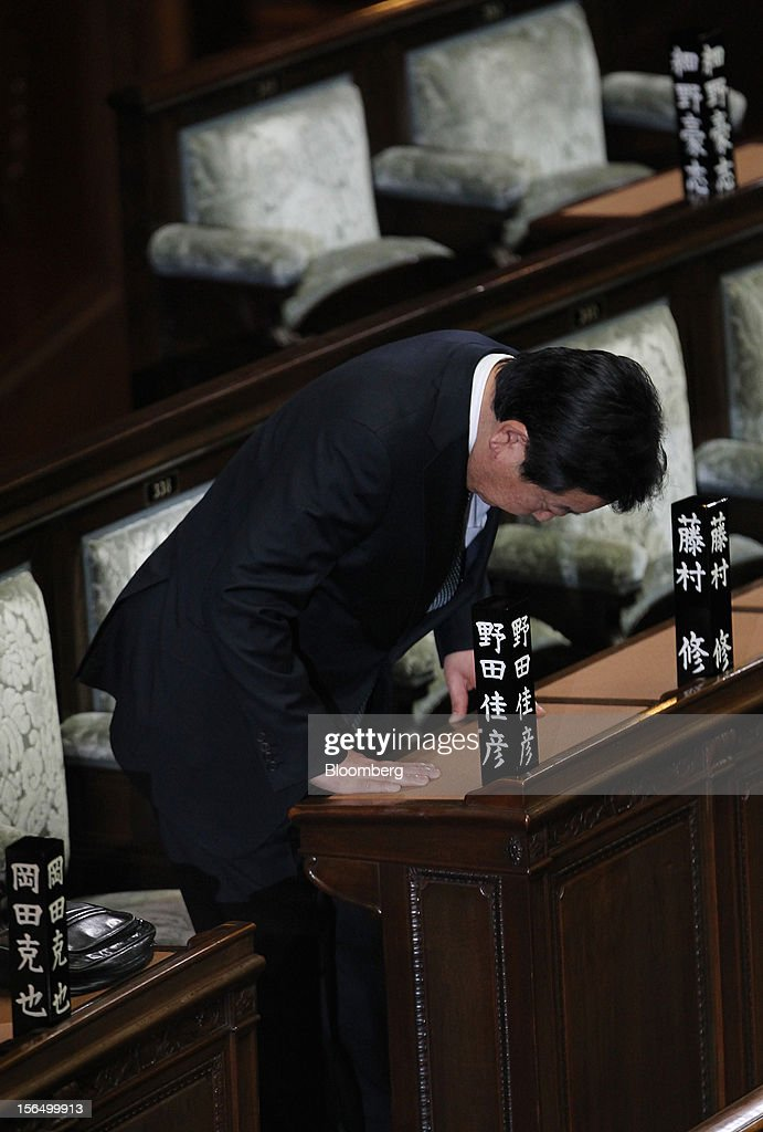 Yoshihiko Noda, Japan's prime minister, bows as he arrives to attend a plenary session at the Lower House of Parliament in Tokyo, Japan, on Friday, Nov. 16, 2012. Noda dissolved the lower house of parliament today after the upper house passed a bill to issue bonds to finance spending for the rest of this fiscal year, following a months-long impasse that left the government weeks away from running out of money. The election will be held on Dec. 16. Photographer: Junko Kimura/Bloomberg via Getty Images