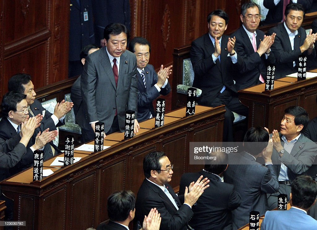 Yoshihiko Noda, president of the Democratic Party of Japan (DPJ), standing third from left, is applauded after being elected Japan's prime minister at the lower house of parliament in Tokyo, Japan, on Tuesday, Aug. 30, 2011. Noda becomes Japan's sixth leader in five years, seeking a consensus to raise taxes to pay for rebuilding from the March earthquake and nuclear disaster and reduce the world's largest debt. Photographer: Haruyoshi Yamaguchi/Bloomberg via Getty Images