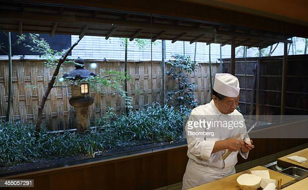 Yoshihiro Murata master chef for Kikunoi Japanese restaurant and chairman of the Japanese Culinary Academy cuts a turnip in the restaurant kitchen...