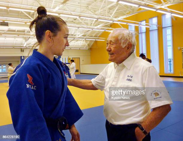Yoshihiro Uchida coach of the US judo team in the 1964 Tokyo Olympics speaks to his charge Marti Malloy a bronze medalist in the women's 57kilogram...