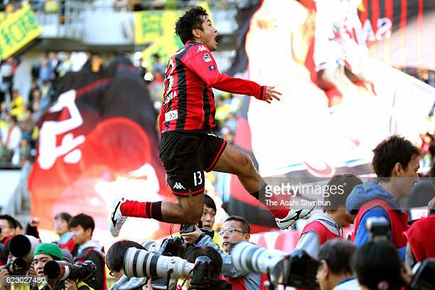 Yoshihiro Uchimura of Consadole Sapporo jumps over photographers to celebrate scoring his team's second goal at the injury time during the JLeague...