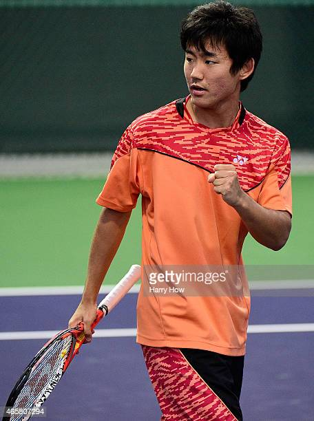 Yoshihito Nishioka of Japan reacts to winning a point at the net against Mischa Zverev of Germany during qualifying for the BNP Paribas Open tennis...