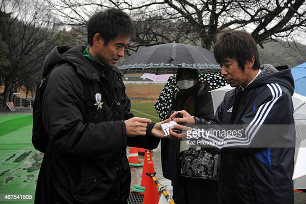 Yoshikatsu Kawaguchi of FC Gifu gives his autograph to a supporter during the preseason friendly match between FC Gifu and Fukuoka University at...