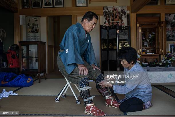 Yoshikatsu Mottate 72 is assisted by his wife Masako as he gets dressed into traditional clothing at his home prior to taking part in the Soma Nomaoi...