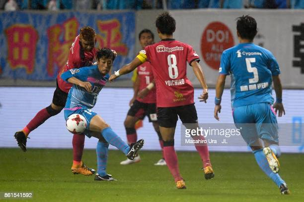 Yoshiki Takahashi of Sagan Tosu and Souza of Cerezo Osaka compete for the ball during the JLeague J1 match between Sagan Tosu and Cerezo Osaka at...