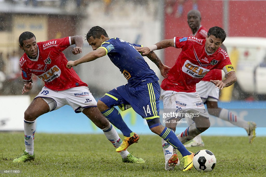 Yoshimar Yotun (C) of Sporting Cristal struggles for the ball with Nicolas Medina (R) and Omar Reyes (L) of Union Comercio during a match between Union Comercio and Sporting Cristal as part of round 14 of Torneo Apertura 2014 at IPD de Moyobamba Stadium on August 24, 2014 in Moyobamba, Peru.