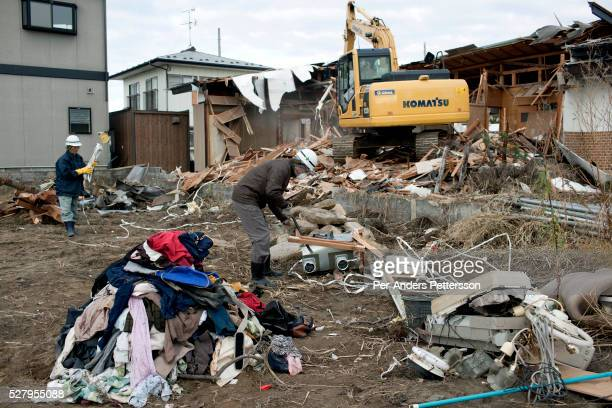 Yoshimito Sugawara works to clear rubble and tear down a house destroyed residential area still not being cleared eight months after the tsunami on...