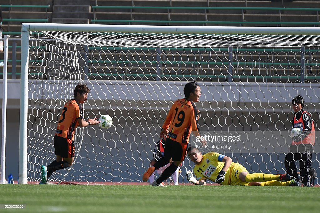 Yoshinari Takagi of FC Gifu has been beaten by Fumitaka Kitatani of Renofa Yamaguchi during the J.League match between FC Gifu and Renofa Yamaguchi at the Nagaragawa Stadium on April 29, 2016 in Nagoya, Japan.