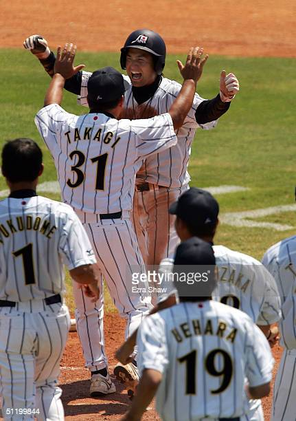 Yoshinobu Takahashi is congratulated by coach Yutaka Takagi and other players after he scored the winning run on a sacrifice fly hit by Michihiro...