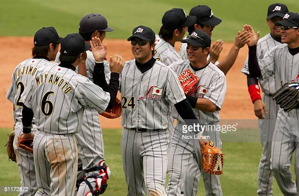 Yoshinobu Takahashi of Japan is congratulated by teammates after Japan defeated Italy in the baseball preliminary game on August 15 2004 during the...