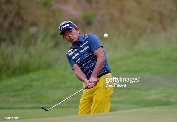 Yoshinobu Tsukada of Japan chips to the 17th green during a continuation of Round One of the 113th US Open at Merion Golf Club on June 14 2013 in...