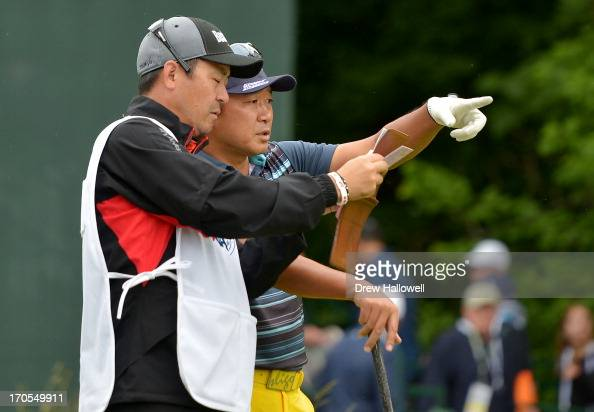 Yoshinobu Tsukada of Japan talks with his caddie during a continuation of Round One of the 113th US Open at Merion Golf Club on June 14 2013 in...
