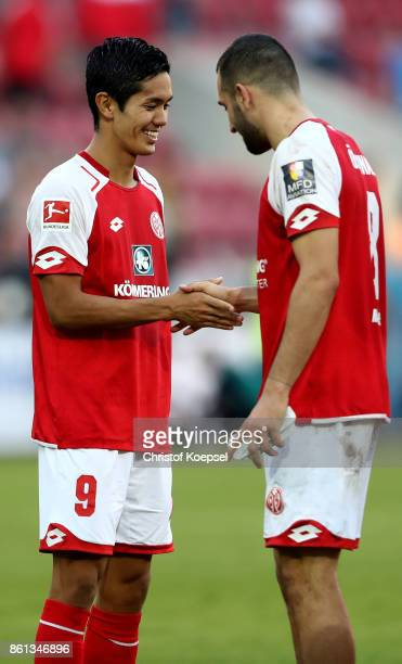 Yoshinori Muto celebrates with Levan Oeztunali of Mainz after winning 32 the Bundesliga match between 1 FSV Mainz 05 and Hamburger SV at Opel Arena...