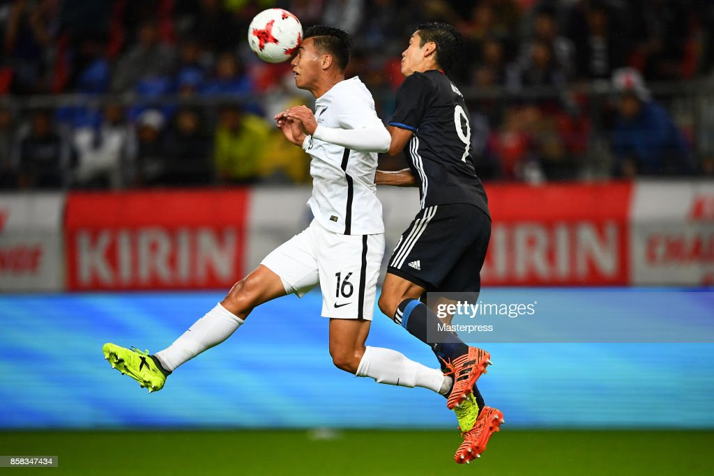 Yoshinori Muto of Japan and Dane Ingham of New Zealand compete for the ball during the international friendly match between Japan and New Zealand at Toyota Stadium on October 6, 2017 in Toyota, Aichi, Japan.