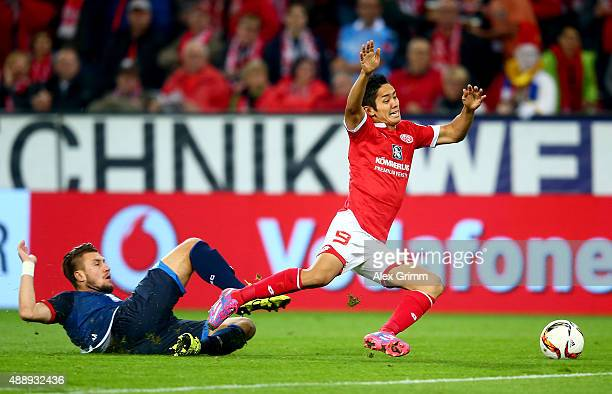 Yoshinori Muto of Mainz and Ermin Bicakcic of Hoffenheim battle for the ball during the Bundesliga match between 1 FSV Mainz 05 and 1899 Hoffenheim...