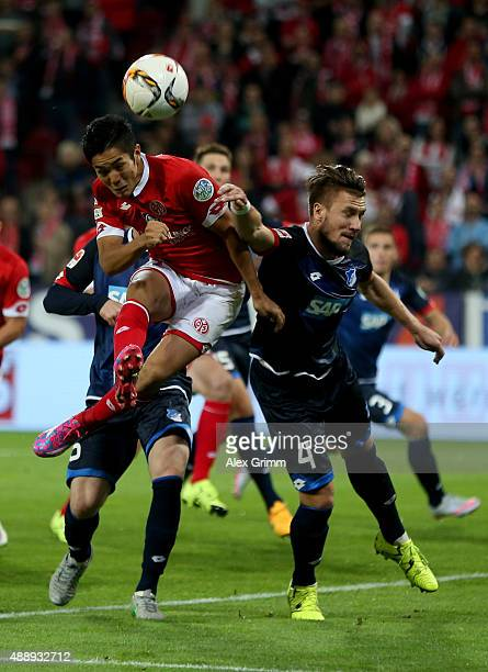 Yoshinori Muto of Mainz and Ermin Bicakcic of Hoffenheim head for the ball during the Bundesliga match between 1 FSV Mainz 05 and 1899 Hoffenheim at...